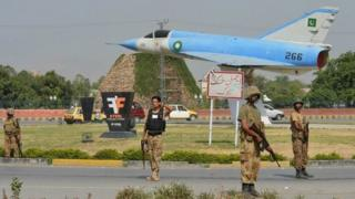 Pakistani soldiers patrol a street near a retired Pakistan Air Force Dassault Mirage III aircraft, on display as a gate guardian, near Peshawar International Airport on June 26, 2014