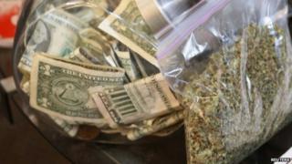 File photo: A bag of marijuana next to a money jar, Colorado, 31 December 2013