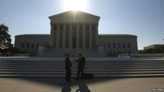 Two men talk as the sun rises over the Supreme Court in Washington 23 June 2014