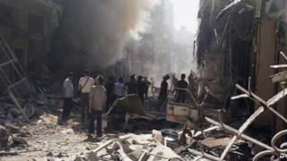 Syrians inspected a site amid the rubble of destroyed buildings following a Syrian government airstrike at Karm al-Jabal area in Aleppo, Syria, on 26 June 2014
