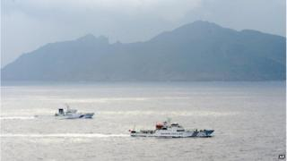 In this 23 April 2013 file photo, a Japan Coast Guard vessel (left) sails along with a Chinese surveillance ship near the disputed islands called Senkaku in Japan and Diaoyu in China in the East China Sea.