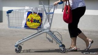 A woman with a shopping trolley and Lidl shopping bag