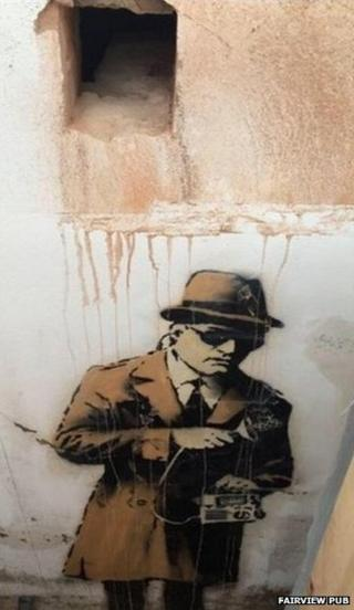 Hole cut in wall next to Banksy artwork