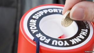 Somebody putting a pound coin into a charity tin