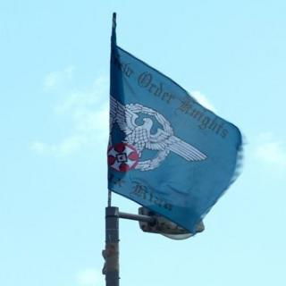 The flag bears the words New Order Knights and Ku Klux Klan