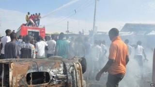 People gather at the scene of a car bomb explosion, at the central market, in Maiduguri, Nigeria, Tuesday, July 1, 2014.