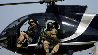 Blackwater employees in a helicopter over Iraq in February 2005