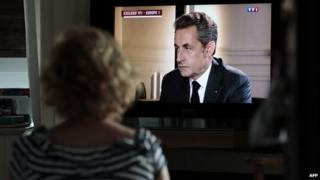 A woman watches a televised interview with former French President Nicolas Sarkozy