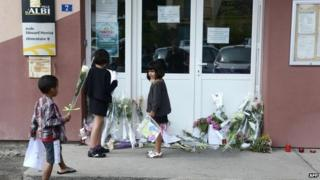 Children leave flowers in front of the school