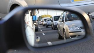 Cars reflected in a wing mirror
