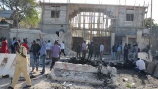 File photo: Onlookers and a Somali soldier stand amid the debris after an attack in front of the presidential palace in Mogadishu, 21 February 2014
