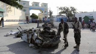 Somali government soldiers stand near the wreckage of a car destroyed during an attack at the presidential palace in the capital Mogadishu July 9, 2014.