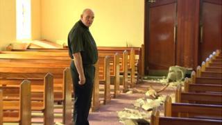 Father Michael Murray surveys the damage