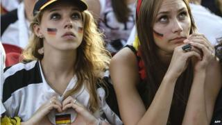 German fan forms a heart with her hands that frames the German national flag during World Cup quarter-final match between Germany and France at the Brandenburg Gate in Berlin, Germany on 4 July 2014