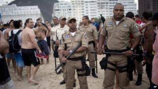 Police stand guard as Argentina soccer fans gather on Copacabana beach during the World Cup in Rio de Janeiro, Brazil, 11 July 2014