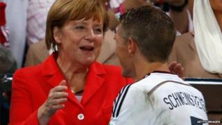 German Chancellor Angela Merkel congratulates Bastian Schweinsteiger of Germany during the medal ceremony after the 2014 FIFA World Cup Brazil Final match between Germany and Argentina at Maracana in Rio de Janeiro, Brazil, 13 July 2014