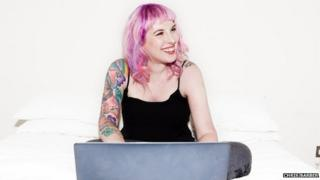 Kat Williams, blogger with pink hair and tattoos sits at her laptop