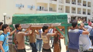Egyptians carried the coffin of a person killed in El-Arish in Northern Sinai on 14 July 2014