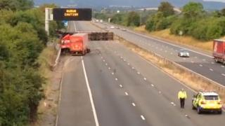 The scene of the accident showing two lorries, one of which has flipped onto its side blocking all three lanes and the hard shoulder
