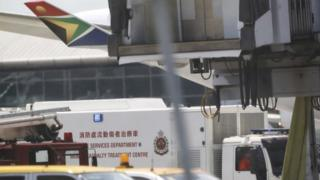 Fire service vehicle parks in front of the South African Airways flight SA286 in the Hong Kong International Airport, 16 July 2014