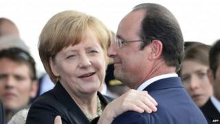 French President Francois Hollande (R) embraces German Chancellor Angela Merkel at the international D-Day commemoration ceremony in Ouistreham (June 2014)