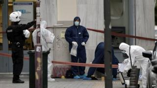 Police officers collect evidence after the shooting in central Athens