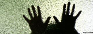 Boy's hands silhouetted through glass door