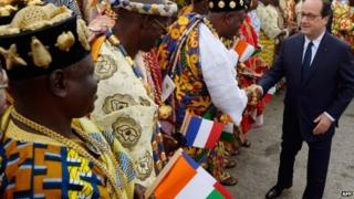 French President Francois Hollande shakes hands with representatives of traditional authorities upon his arrival in Abidjan on 17 July 2014
