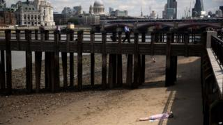 A woman sunbathes on the banks of the river Thames in London.