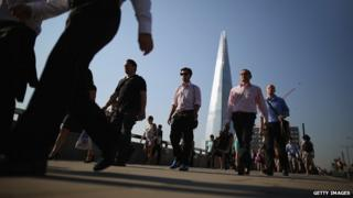 Pedestrians walking across a London bridge with Shard in background