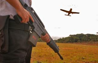 A man holds a gun as a plane passes overhead