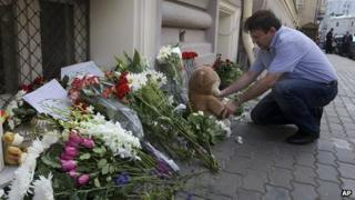 A man lays a stuffed bear among flowers outside the Dutch embassy in Moscow