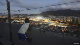 A boy watches from the Mangueira favela during the World Cup final on 13 July