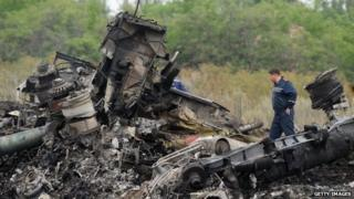 Rescuers stood among the rubble of Malaysian Airlines flight 17 in Ukraine on 18 July 2014