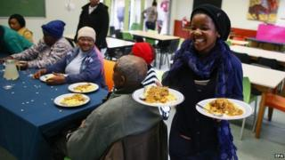 A South African girl serves a free meal to the elderly at the Masiphumelele Library, on the occasion of Mandela Day, in the impoverished community of Masiphumelele in Cape Town, South Africa, 18 July 2014.
