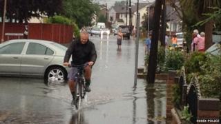 A man rides a bike through flood water