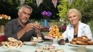 Paul Hollywood and Mary Berry at a table piled high with cakes