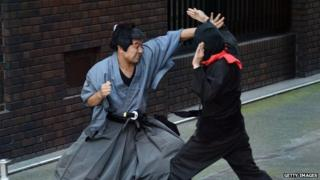 Samurai and ninja actors stage a fight on the streets of Tokyo