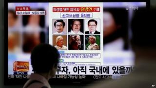 A woman looks at a 'wanted' poster for Yoo Byung-eun, shown on a South Korean TV news channel - 26 May 2014