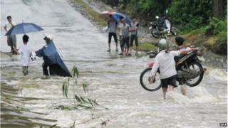A photo made available 22 July 2014 shows people walk through a flooded area in Lao Cai, northern Vietnam, 21 July 2014.