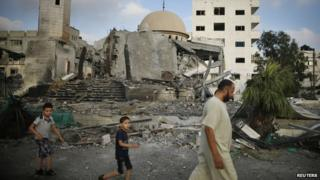 Palestinians walk past a ruined mosque in the Gaza Strip