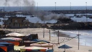 Smoke billows from a beach shack following an Israeli military strike on Gaza City, 16 July 2014