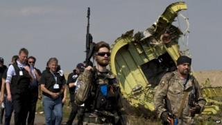 A pro-Russian rebel holds a gun passing by plane wreckage as members of the OSCE mission to Ukraine arrive for a media briefing at the crash site of MH17, July 22