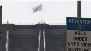 A bleached US flag flies over the Brooklyn Bridge.