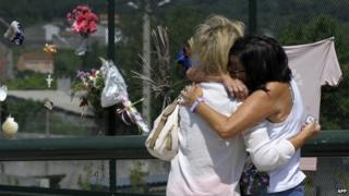 Relatives of victims of the Santiago de Compostela train crash hug at the accident site near Santiago de Compostela on 23 July 2014.