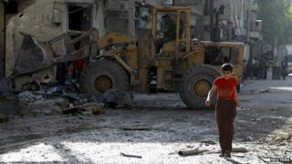 """A boy walks along a damaged road as a front loader removes rubble at a site hit by what activists said was shelling by forces loyal to Syria""""s President Bashar al-Assad in the al-Myassar neighbourhood of Aleppo July 14, 2014"""