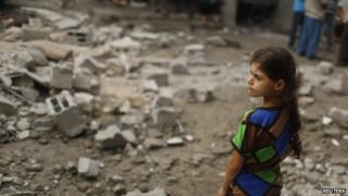 A Palestinian girl looks at houses which witnesses said were damaged in an Israeli air strike that killed two children, in the northern Gaza Strip, 24 July 2014