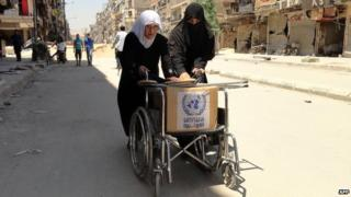 """Residents of Syria""""s Yarmuk Palestinian refugee camp, south of Damascus, use a wheelchair to carry a box of goods distributed by the United Nations Relief and Works Agency (UNRWA) on July 17"""