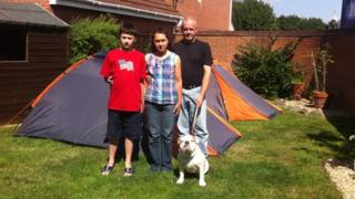 The Softely family and their dog standing in front of tents in their back garden