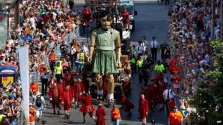 The girl giant marionette is steered through the centre of Liverpool